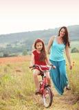 Madre con il suo bambino sulla bicicletta Immagine Stock