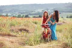 Madre con il suo bambino sulla bicicletta Immagini Stock
