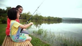 Madre con il suo lato della figlia vicino mentre pescando nel lago Concetto dei bambini di collegamento con la natura video d archivio