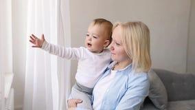 Madre con il suo neonato che esamina finestra stock footage