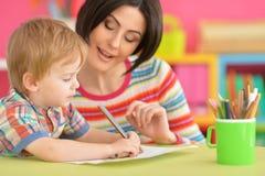 Madre con il suo tiraggio del figlio con le matite fotografia stock