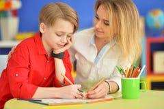 Madre con il suo tiraggio del figlio con le matite immagini stock libere da diritti