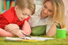 Madre con il suo tiraggio del figlio con le matite fotografie stock libere da diritti