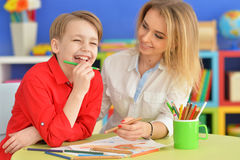Madre con il suo tiraggio del figlio con le matite fotografia stock libera da diritti
