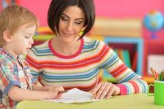 Madre con il suo tiraggio del figlio con le matite fotografie stock