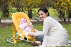 Madre con l'infante in sedia Fotografia Stock
