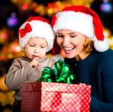 Madre con la caja del control del pequeño niño con los regalos del Año Nuevo Fotografía de archivo