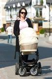 Madre con la carrozzina Immagini Stock Libere da Diritti