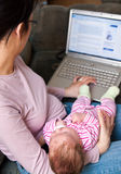 Madre con la computadora portátil y bebé Imágenes de archivo libres de regalías