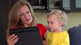 Madre con la conversación video del pequeño comienzo de la hija con el padre en la tableta almacen de metraje de vídeo