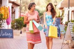 Madre con la figlia adulta sui sacchetti della spesa di trasporto della via Fotografia Stock Libera da Diritti