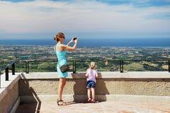 Madre con la figlia alla piattaforma di osservazione di San Marino Mamma che prende la foto del paesaggio con lo smartphone Bambi Fotografia Stock
