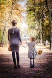 Madre con la figlia che cammina nel parco nel tenersi per mano di autunno Fotografia Stock Libera da Diritti