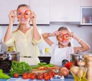Madre con la figlia che cucina le verdure Immagine Stock