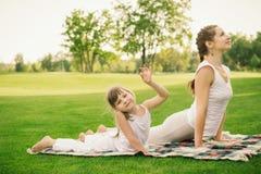 Madre con la figlia che fa esercizio di yoga fotografie stock libere da diritti