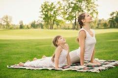 Madre con la figlia che fa esercizio di yoga fotografia stock libera da diritti