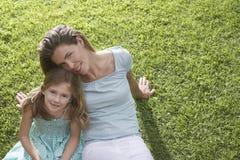 Madre con la figlia che si siede sull'erba Immagini Stock