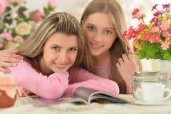 Madre con la figlia con la rivista Immagine Stock