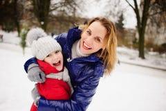 Madre con la figlia contro fondo dell'iarda innevata della città Immagini Stock Libere da Diritti