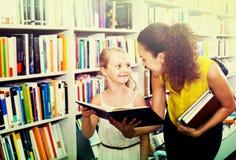 Madre con la figlia in libreria Fotografia Stock Libera da Diritti