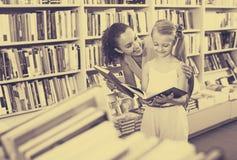 Madre con la figlia in libreria Immagini Stock