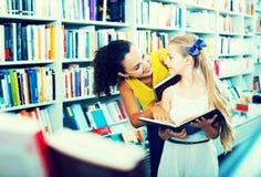 Madre con la figlia in libreria Immagini Stock Libere da Diritti