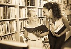 Madre con la figlia in libreria Immagine Stock