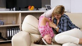 Madre con la hija adolescente que ríe y que se divierte en la sala de estar almacen de metraje de vídeo