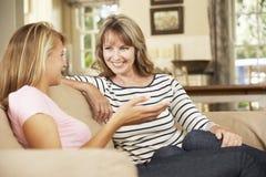 Madre con la hija adolescente que se sienta en Sofa At Home Chatting Fotos de archivo