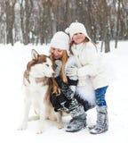 Madre con la hija con el perro de los perros esquimales Foto de archivo
