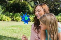 Madre con la hija con un molinillo de viento en el parque Imágenes de archivo libres de regalías