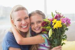 Madre con la hija de abarcamiento del ramo en casa Imágenes de archivo libres de regalías