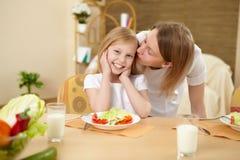 Madre con la hija del adolescente que tiene comida en casa Imagenes de archivo