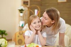 Madre con la hija del adolescente que tiene comida en casa Fotos de archivo