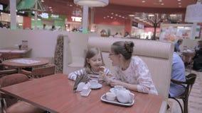 Madre con la hija en café Comiendo el helado, hablando, divirtiéndose almacen de video