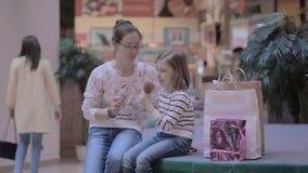 Madre con la hija en café Comiendo el helado, hablando, divirtiéndose metrajes