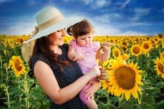 Madre con la hija en el campo con los girasoles Foto de archivo