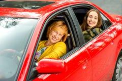 Madre con la hija en el coche rojo Foto de archivo libre de regalías