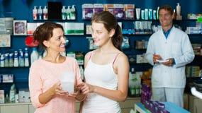 Madre con la hija en farmacia Imagen de archivo libre de regalías