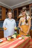 Madre con la hija en la cocina foto de archivo