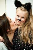Madre con la hija en traje del gatito Imagenes de archivo