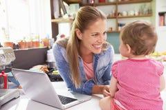 Madre con la hija joven que usa el ordenador portátil en cocina Imagenes de archivo