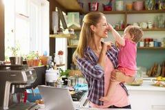 Madre con la hija joven que usa el ordenador portátil en cocina Fotografía de archivo