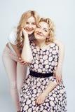 Madre con la hija junta que plantea la sonrisa feliz aislada en el fondo blanco con el copyspace, concepto de la gente de la form Imagenes de archivo