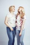 Madre con la hija junta que plantea la sonrisa feliz aislada en el fondo blanco con el copyspace, concepto de la gente de la form Fotografía de archivo