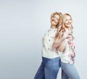 Madre con la hija junta que plantea la sonrisa feliz aislada en el fondo blanco con el copyspace, concepto de la gente de la form Foto de archivo libre de regalías