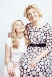 Madre con la hija junta que plantea la sonrisa feliz aislada en el fondo blanco con el copyspace, concepto de la gente de la form Fotos de archivo libres de regalías