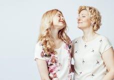 Madre con la hija junta que plantea la sonrisa feliz aislada en el fondo blanco con el copyspace, concepto de la gente de la form Imagen de archivo