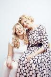 Madre con la hija junta que plantea la sonrisa feliz aislada en el fondo blanco con el copyspace, concepto de la gente de la form Fotos de archivo