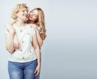 Madre con la hija junta que plantea la sonrisa feliz aislada en el fondo blanco con el copyspace, concepto de la gente de la form Fotografía de archivo libre de regalías